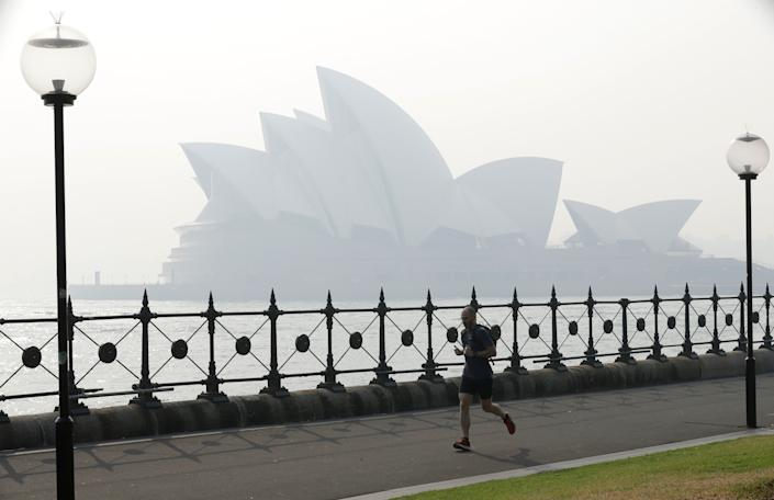 A jogger runs in the morning as smoke haze hangs over the Sydney Opera House in Sydney, on Nov. 21, 2019. (Photo: ASSOCIATED PRESS)
