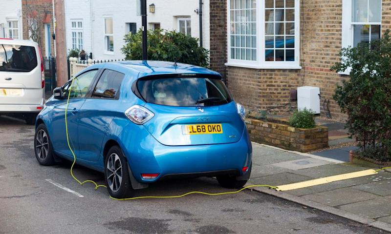 Renault Zoe being charged using an electrical cable from a house.