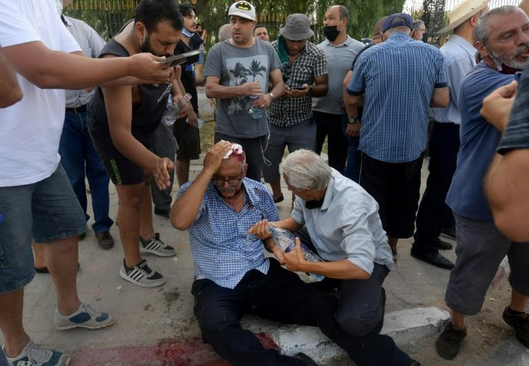 A supporter of the Ennahda party stems his wound from a stone thrown during a protest outside the parliament building in Tunis on Monday