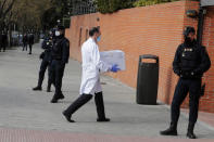 FILE - In this Sunday, Dec. 27, 2020 file photo, Police stand by the entrance of a nursing home as a box of some of the first Pfizer coronavirus vaccines arrives in Madrid, Spain. Spain plans to receive over 4.5 million doses of the vaccine over the next three months, enough it says to immunize just over 2.2 million people. The government estimates that this first phase will be enough to cover nursing home residents and workers, followed by health workers in general and people with disabilities. (AP Photo/Paul White, File)