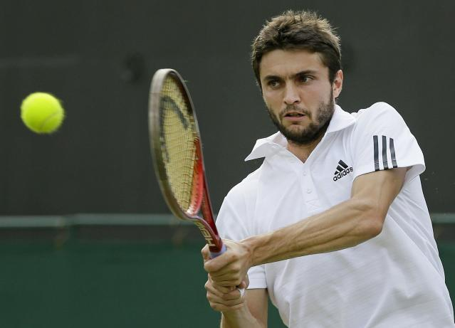 Gilles Simon of France plays a return to Feliciano Lopez of Spain during their Men's first round singles match at the All England Lawn Tennis Championships in Wimbledon, London, Tuesday, June 25, 2013. (AP Photo/Alastair Grant)
