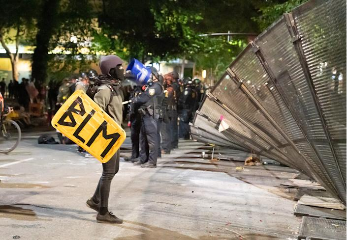A protester inspects the torn-down fence outside the federal courthouse in Portland, Ore., in the early morning of July 26, 2020.