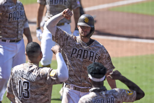 San Diego Padres' Wil Myers (4) is congratulated by Manny Machado (13) and Jurickson Profar (10) after hitting a three-run home run during the sixth inning of a baseball game against the Seattle Mariners Sunday, Sept. 20, 2020, in San Diego. (AP Photo/Denis Poroy)