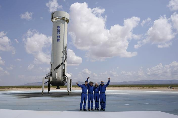 Oliver Daemen, from left, Jeff Bezos, founder of Amazon and space tourism company Blue Origin, Wally Funk and Bezos' brother Mark pose for photos in front of the rocket that landed safely after their launch from the spaceport near Van Horn, Texas, Tuesday, July 20, 2021. (AP Photo/Tony Gutierrez)