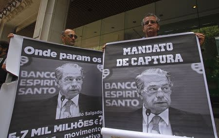 Protesters hold up posters with the image of former Banco Espirito Santo (BES) CEO Ricardo Salgado during a demonstration at BES's headquarters office in downtown Lisbon in this August 9, 2014 file photo. REUTERS/Hugo Correia/Files
