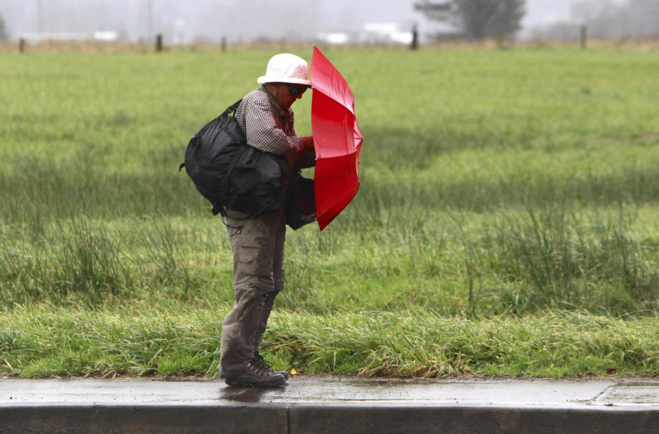 A pedestrian holds his umbrella during intense weather in Tillamook, Oregon December 10, 2014. High winds and heavy rain are expected through Thursday. REUTERS/Steve Dipaola (UNITED STATES – Tags: ENVIRONMENT)