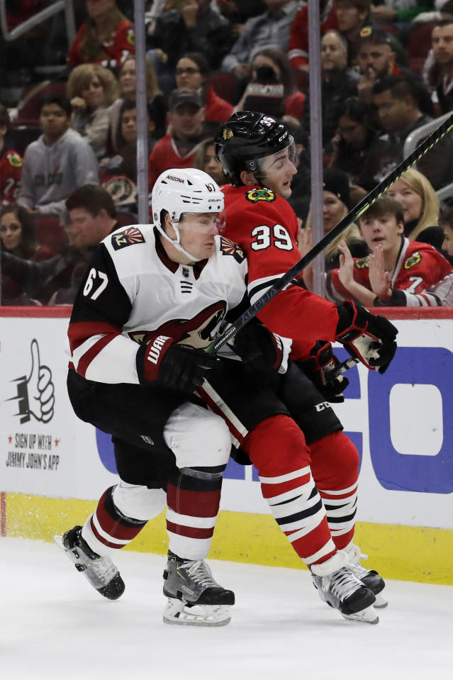 Chicago Blackhawks defenseman Dennis Gilbert, right, is checked by Arizona Coyotes left wing Lawson Crouse during the first period of an NHL hockey game Sunday, Dec. 8, 2019, in Chicago. (AP Photo/Nam Y. Huh)