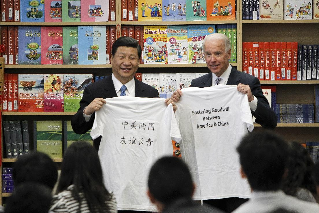 Chinese Vice President Xi Jinping and Vice President Joe Biden hold t-shirts given to them by students during their visit to the International Studies Learning Center in South Gate, Calif., Friday, Feb. 17, 2012. (AP Photo/Damian Dovarganes)