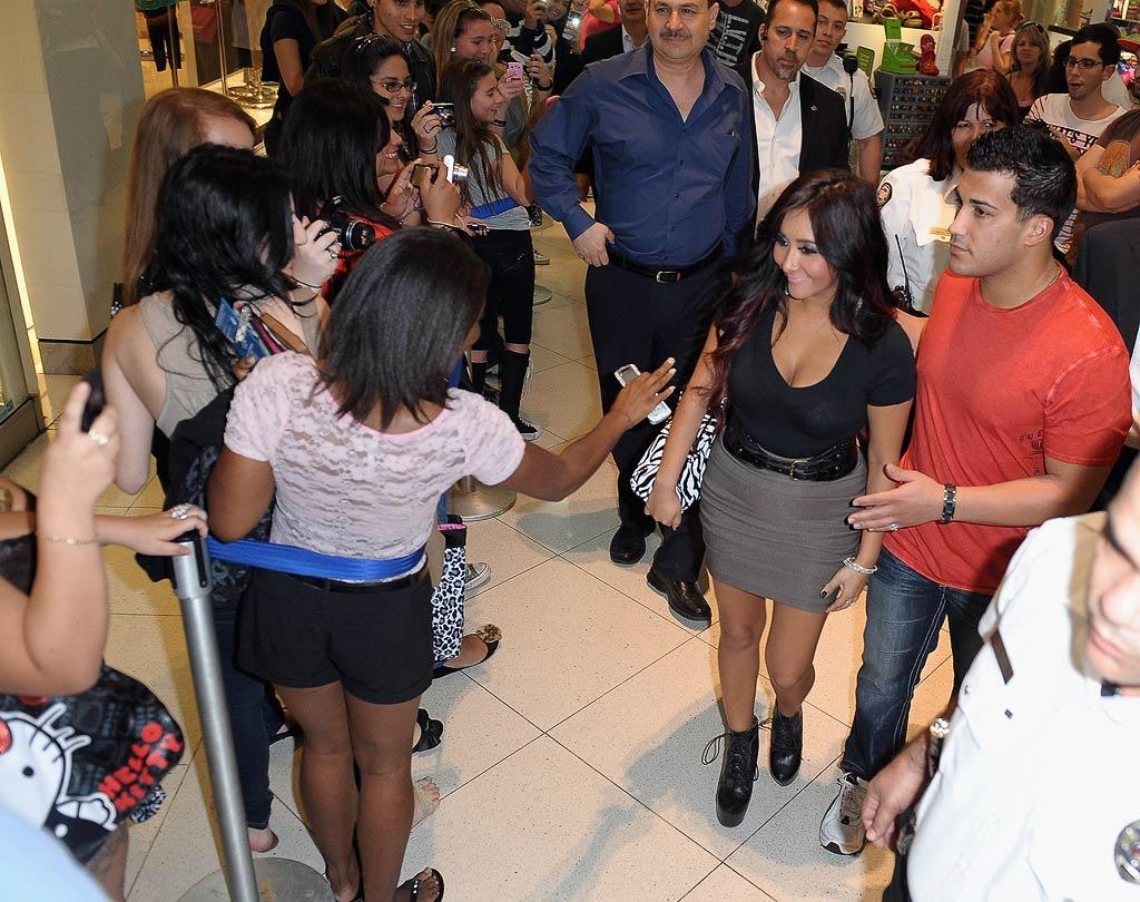 """Nicole """"Snooki"""" Polizzi, escorted by her boyfriend Jionni LaValle, pimped her new perfume, Snooki, during an appearance at Perfumania in the Dolphin Mall in Miami, Florida, on Tuesday. The """"Jersey Shore"""" star is on a mini-mall tour to persuade people to buy her scent this holiday season. (12/06/2011)"""