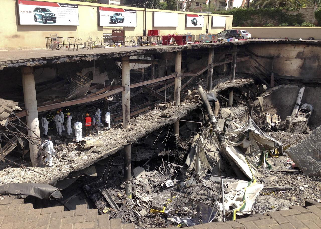 Forensics investigators work next to the collapsed upper car park at the Westgate Mall in Nairobi, Kenya Tuesday, Oct. 1, 2013. Kenyan President Uhuru Kenyatta says Kenya will keep its troops in Somalia to help that country's beleaguered government battle the armed Islamic extremist group al-Shabab, which attacked the mall in Nairobi on Sept. 21 claiming at least 67 lives. (AP Photo/Jason Straziuso)