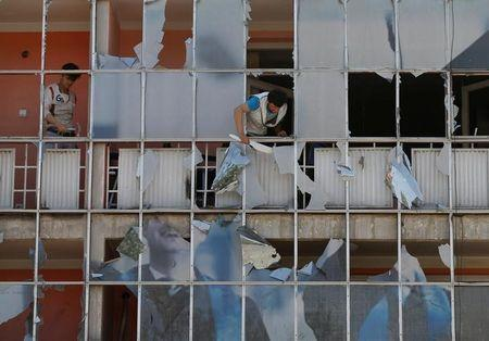 An Afghan man removes fragments of glass from a building after a suicide attack in Kabul, Afghanistan July 24, 2017. REUTERS/Mohammad Ismail