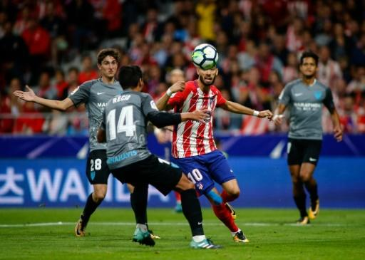 Atletico Madrid's midfielder Yannick Ferreira-Carrasco (C) vies with Malaga's midfielder Jose Recio (L) during the Spanish league football match September 16, 2017