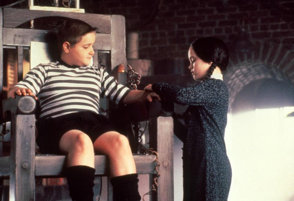 Jimmy Workman sitting in a chair while Christina Ricci ties his arm.