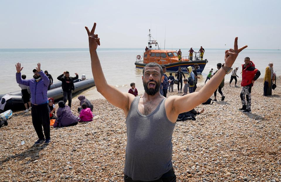 A man gestures as a group of people thought to be migrants make their way up the beach (Gareth Fuller/PA) (PA Wire)