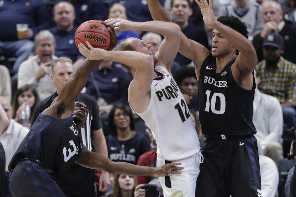 Purdue's Evan Boudreaux (12) is defended by Butler's Kamar Baldwin (3) and Bryce Nze (10) during the second half of an NCAA college basketball game, Saturday, Dec. 21, 2019 in Indianapolis. Butler won 70-61. (AP Photo/Darron Cummings)