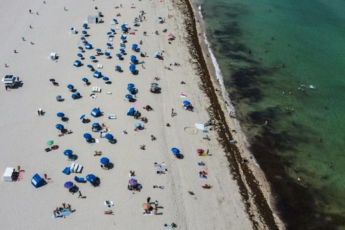 An aerial view shows people on the sand in Miami Beach, Florida, US. (AFP Photo/CHANDAN KHANNA)