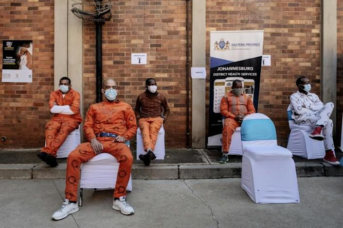 Prisoners wait to get their dose of the Johnson & Johnson vaccine at Johannesburg's Medium Correctional Center on July 20