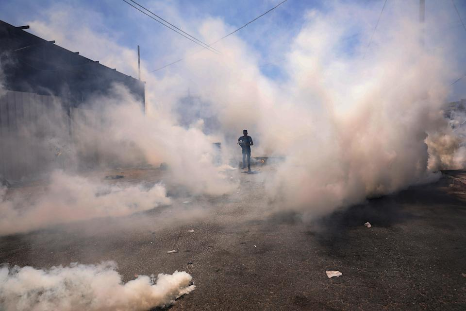 A Palestinian protester seeks cover from tear gas during clashes with Israeli troops after a protest against Israeli settlements at Beta village near the West Bank City of Nablus (EPA)