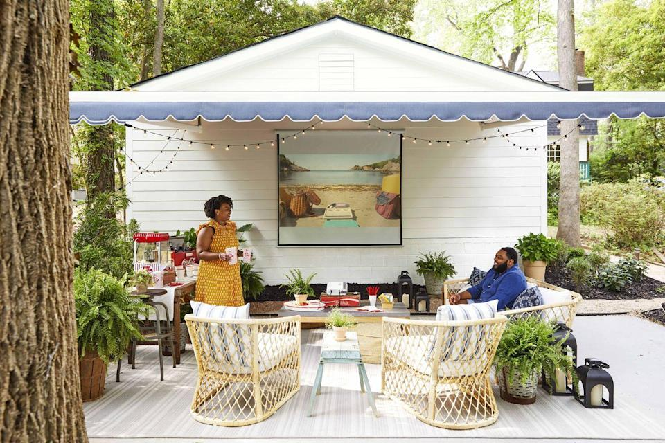 """<p>For the Fords, any night is movie night, so an established spot for movie-watching was high on the backyard wish list. To turn the wide-open area behind the garage into a comfortable """"room,"""" the couple started by defining the space. A large water-and-stain-resistant braided rug woven of <a href=""""https://www.sunbrella.com/outdoor-living"""" rel=""""nofollow noopener"""" target=""""_blank"""" data-ylk=""""slk:Sunbrella"""" class=""""link rapid-noclick-resp"""">Sunbrella</a> yarns provides the space-defining base, while a chambray blue <a href=""""https://www.sunbrella.com/outdoor-living"""" rel=""""nofollow noopener"""" target=""""_blank"""" data-ylk=""""slk:Sunbrella"""" class=""""link rapid-noclick-resp"""">Sunbrella</a> retractable awning cozies things up and shades the pull-down screen. """"The scalloped awning gives it this very preppy and chic feel, yet it's still casual,"""" says Victoria. <br><strong><br>Get the Look: </strong><br><strong>Retractable Awning:</strong> <a href=""""https://www.eclipseawning.com/products/eclipse-motorized-retractable-awning/"""" rel=""""nofollow noopener"""" target=""""_blank"""" data-ylk=""""slk:Sunbrella &quot;Lapis&quot; by Eclipse Awning"""" class=""""link rapid-noclick-resp"""">Sunbrella """"Lapis"""" by Eclipse Awning</a><strong><br>Rug:</strong> <a href=""""https://www.colonialmills.com/collection-colors/1232"""" rel=""""nofollow noopener"""" target=""""_blank"""" data-ylk=""""slk:Sunbrella &quot;Southport Stripe&quot; in Ash by Colonial Mills"""" class=""""link rapid-noclick-resp"""">Sunbrella """"Southport Stripe"""" in Ash by Colonial Mills</a><strong><br>Sofa and Chairs:</strong> <a href=""""https://go.redirectingat.com?id=74968X1596630&url=https%3A%2F%2Fwww.serenaandlily.com%2Fcapistrano-sofa---light-dune%2Fm13244.html%23q%3Dcapistrano%26start%3D6&sref=https%3A%2F%2Fwww.countryliving.com%2Fhome-design%2Fhouse-tours%2Fg36730466%2Fmakeover-takeover-backyard%2F"""" rel=""""nofollow noopener"""" target=""""_blank"""" data-ylk=""""slk:&quot;Capistrano&quot; (upholstered in Sunbrella's &quot;Canvas White&quot; fabric) by Serena & Lily"""" class=""""link rapid-noclick-resp"""">""""Capist"""