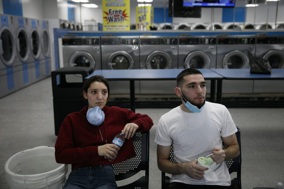 A couple watches TV while doing their laundry amid the coronavirus pandemic in the Vermont Square neighborhood of Los Angeles, Thursday, May 21, 2020. While most of California took another step forward to partly reopen in time for Memorial Day weekend, Los Angeles County didn't join the party because the number of coronavirus cases has grown at a pace that leaves it unable to meet even the new, relaxed state standards for allowing additional businesses and recreational activities. (AP Photo/Jae C. Hong)