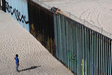 A migrant looks at the border fence between Mexico and the United States in Tijuana