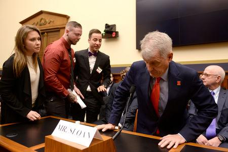 "FILE PHOTO: Wells Fargo employees try to engage CEO Tim Sloan before he testifies at a House Financial Services Committee hearing titled: ""Holding Megabanks Accountable: An Examination of Wells Fargo's Pattern of Consumer Abuses"" in Washington, U.S. March 12, 2019. REUTERS/Erin Scott/File Photo"
