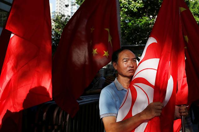<p>A pro-China supporter holds a Hong Kong flag he tries to stop pro-democracy activists from protesting and demanding the release of Chinese Nobel rights activist Liu Xiaobo, during Chinese President Xi Jinping's visit, in Hong Kong, China July 1, 2017. (Photo: Tyrone Siu/Reuters) </p>