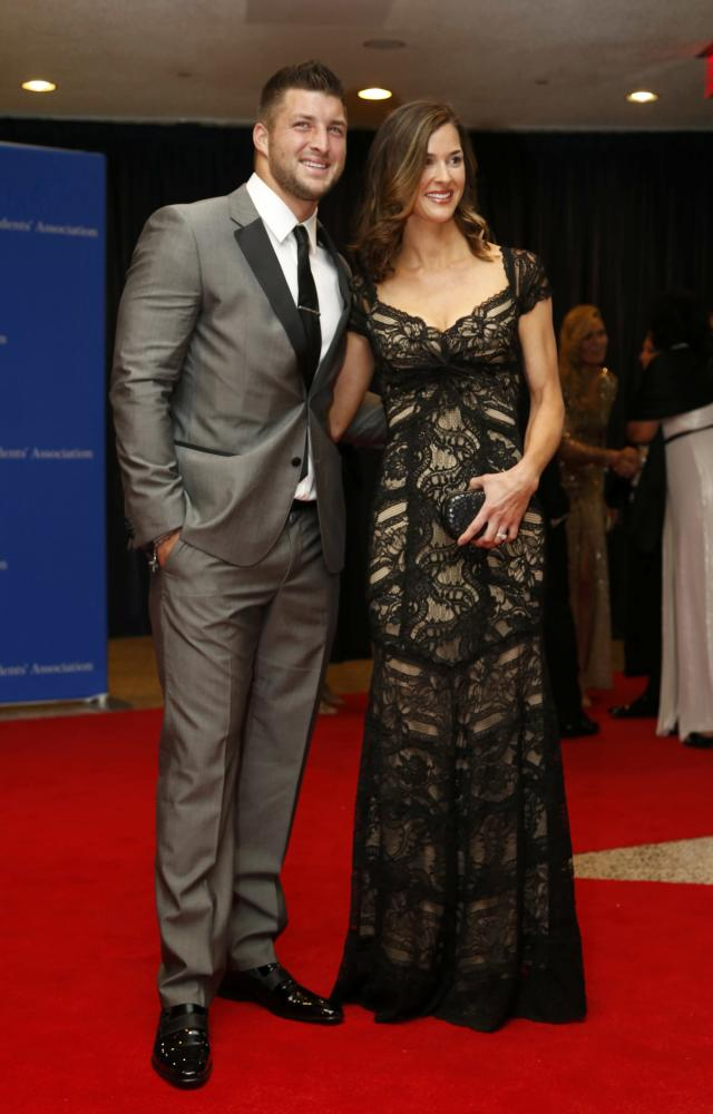 Football player Tim Tebow and guest arrive on the red carpet at the annual White House Correspondents' Association Dinner in Washington, May 3, 2014. REUTERS/Jonathan Ernst (UNITED STATES - Tags: POLITICS MEDIA SPORT ENTERTAINMENT SOCIETY)