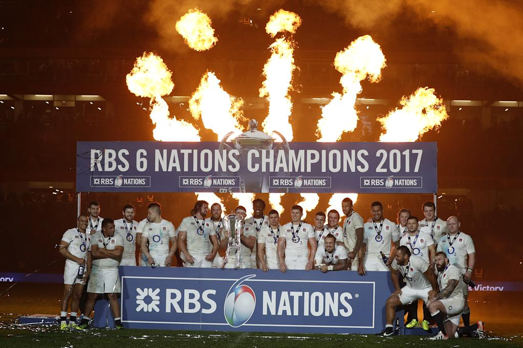 England players celebrate with the trophy after winning the Six Nations Championship on the pitch after the Six Nations international rugby union match between Ireland and England at the Aviva Stadium in Dublin on March 18, 2017 (AFP Photo/Adrian DENNIS)