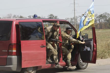 """Soldiers of Ukrainian self-defence battalion """"Azov"""" get out of a car as they arrive at a checkpoint in the southern coastal town of Mariupol, September 5, 2014. REUTERS/Vasily Fedosenko"""