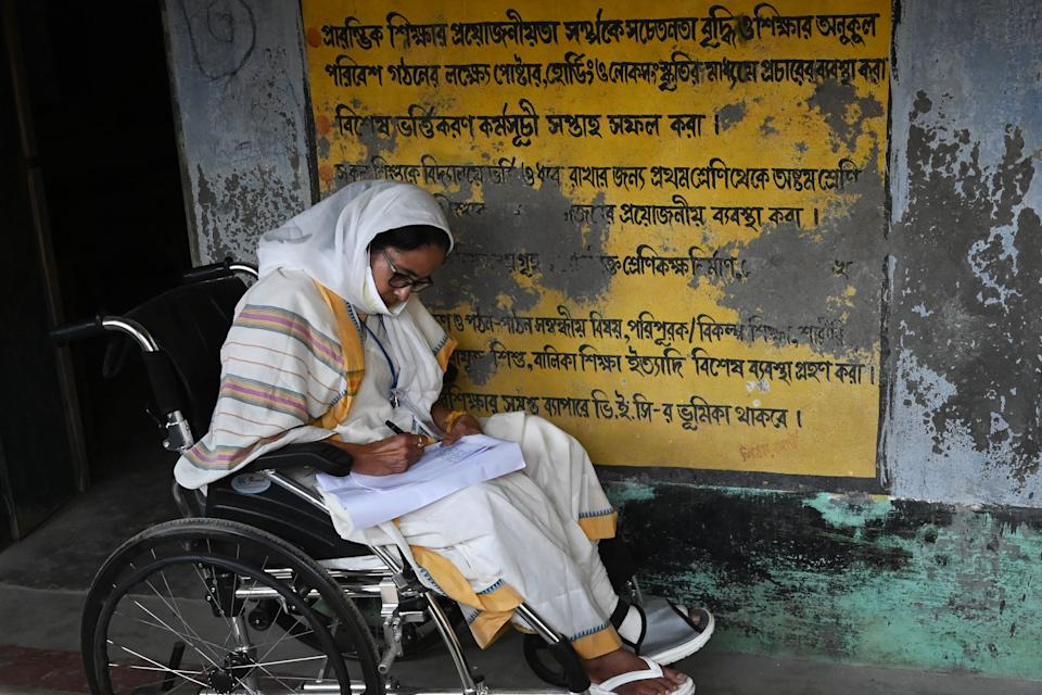 West Bengal's Chief Minister Mamata Banerjee takes notes while sitting in a wheelchair at a polling station during Phase 2 of West Bengal's legislative election in Nandigram on April 1, 2021. (Photo by DIBYANGSHU SARKAR / AFP) (Photo by DIBYANGSHU SARKAR/AFP via Getty Images)