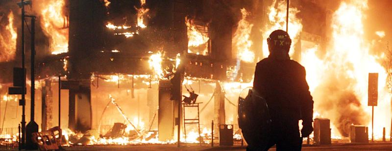 Riot police looks on as fire rages through a building in Tottenham, north London Sunday, Aug. 7, 2011. A demonstration against the death of a local man turned violent and cars and shops were set ablaze. (AP Photo/PA, Lewis Whyld) UNITED KINGDOM OUT, NO SALES,  NO ARCHIVES