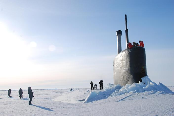In this March 19, 2011 photo released by the U.S. Navy, crew members look out from the USS Connecticut, a Sea Wolf-class nuclear submarine, after it surfaced through ice in the Arctic Ocean. The U.S. and other countries are building up their military presence in the Arctic to help exploit its riches - and protect shifting borders. (AP Photo/U.S. Navy, Cmdr. Christy Hagen)