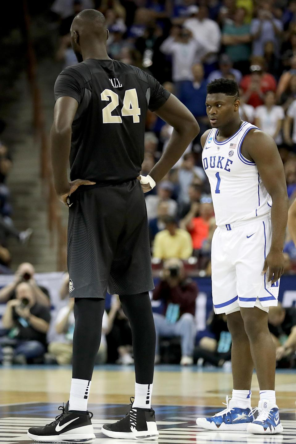 <p>Tacko Fall #24 of the UCF Knights and Zion Williamson #1 of the Duke Blue Devils look on during the first half in the second round game of the 2019 NCAA Men's Basketball Tournament at Colonial Life Arena on March 24, 2019 in Columbia, South Carolina. (Photo by Streeter Lecka/Getty Images) </p>