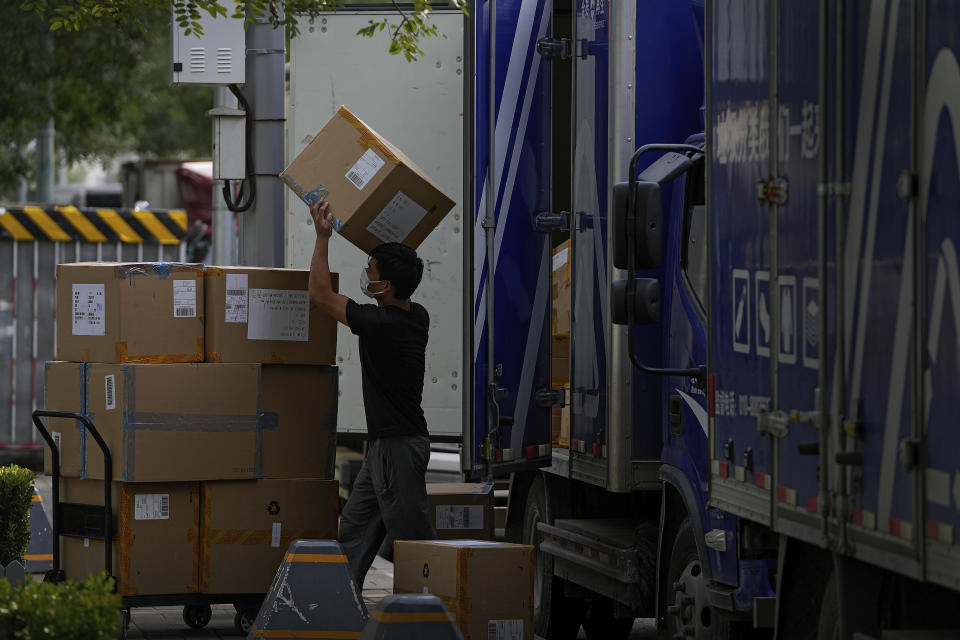 A worker loads boxes of goods from a truck near a shopping mall in Beijing, Wednesday, Oct. 13, 2021. China's import and export growth slowed in September amid shipping bottlenecks and other disruptions combined with coronavirus outbreaks. (AP Photo/Andy Wong)