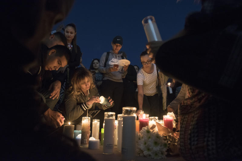 Mourners place candles and flowers on the ground during a candlelight vigil. (Martin S. Fuentes for HuffPost)