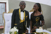 Brian Ngona, left, and Mitchelle Musaraure, pose for a photo after their traditional marriage ceremony in the capital Harare, Zimbabwe Saturday, March 6, 2021. Many people across Africa are rethinking big, bountiful weddings amid the economic ravages of COVID-19 and the coronavirus pandemic is forcing change in communities where family can mean a whole clan and weddings are seen as key in cementing relations between communities. (AP Photo/Tsvangirayi Mukwazhi)