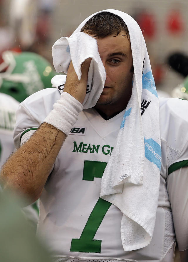 North Texas quarterback Derek Thompson (7) dries his face as he waits on the sidelines for time to expire in an NCAA college football game against Georgia, Saturday, Sept. 21, 2013, in Athens, Ga. Georgia won 45-21. (AP Photo/John Bazemore)