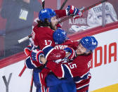 Montreal Canadiens' Josh Anderson (17) celebrates with teammates Paul Byron (41) and Jesperi Kotkaniemi (15) after scoring against the Vegas Golden Knights during overtime in Game 3 of an NHL hockey semifinal series, Friday, June 18, 2021, in Montreal. (Graham Hughes/The Canadian Press via AP)