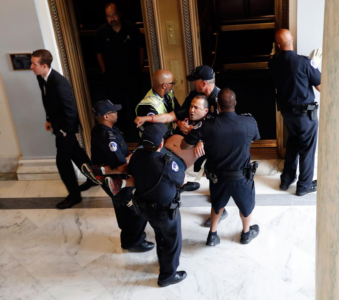 <p>A man is removed from a sit-in outside of Senate Majority Leader Mitch McConnell's office as they protest proposed cuts to Medicaid, Thursday, June 22, 2017 on Capitol Hill in Washington. (Photo: Jacquelyn Martin/AP) </p>