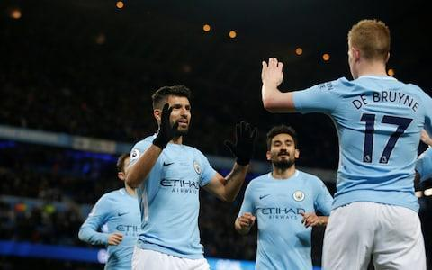 "No wonder Riyad Mahrez was desperate to join this lot. Another win, another avalanche of goals, their lead at the top of the Premier League stretched to a scarcely believable 16 points and another show stopping turn from that serial slaughterer of defenders. When Sergio Aguero received the ball from Phil Foden just outside the penalty area as the clock hit 90 minutes, the young Manchester City midfielder was screaming for it back. Aguero, though, had only one thing in mind at that point and crashed a thunderous strike in off the underside of the crossbar for his fourth goal of an arresting afternoon. The Argentina striker is now just three goals short of a double century for Manchester City and just six shy of bettering his season best goals tally for the club of 33. It is only early February and Aguero already has 28 goals in 32 appearances, half of which have come in his last seven games at the Etihad. Do not let anyone tell you this man is past his best. ""When one guy is able to score four goals, he deserves all the credit,"" Pep Guardiola, the Manchester City manager, said. Guardiola's side now have 72 points and are unbeaten at the Etihad since December 2016. Seven more wins will guarantee the title. The Premier League is widely as the most competitive in Europe but Guardiola is in danger of turning it into a one horse show like Scotland and could become the first to smash the 100 point barrier. When it was put to Guardiola he was making it look easy, he replied: ""So far, yeah. I would like to take that question after 38 games. So far we have 72 points in February so it is a lot. We've enjoyed the last six or seven months but to be admired and loved we have to win the title."" Man City 1 - 0 Leicester (Raheem Sterling, 3 min) Leicester City had barely gained a foothold in the game before they equalised against the run of play. Guardiola will have been disappointed that the goal originated from a misplaced pass from Nicolas Otamendi, who had actually done well to dispossess Fousseni Diabate but he will have admired the subsequent brilliance of Jamie Vardy. Collecting Otamendi's stray pass, Vardy rode challenges from Oleksandr Zinchenko and Ilkay Gundogan, both of whom had slid in to try to win the ball back, before careering towards the penalty area. With Aymeric Laporte backing off, Vardy fired expertly into the far bottom corner. It was a terrific piece of centre-forward play. Man City 1 - 1 Leicester (Jamie Vardy, 24 min) ""He perhaps made a mistake but it's important to have our best players with us,"" Claude Puel, the Leicester City manager, said of Mahrez. ""The most important thing is that he came back to the training session, to the game. Now it's important to look forward and put this behind us."" If Aguero stole the headlines, Kevin De Bruyne ran him close for the man-of-the-match award. It was De Bruyne who fashioned the first three goals with characteristically sublime passes. The match was only three minutes old when Raheem Sterling gave the hosts the lead. Bernardo Silva pulled the ball back to De Bruyne on the right and the Belgian swung in a wonderful cross that eluded Leicester City's defence, the ball flying across the six yard box to the far post where Sterling nipped ahead of Marc Albrighton to steer home. Guardiola – who named three academy graduates among his substitutes a week after being criticised by Gary Neville for denying a youth team player a chance by only naming six substitutes against Burnley - had substituted Sterling immediately after the England forward missed a golden chance at Turf Moor but there was no mistake here. Man City 2 - 1 Leicester (Sergio Agüero, 48 min) Leicester City had barely gained a foothold in the game before they equalised thanks to a terrific piece of centre-forward play from Jamie Vardy, who capitalised on a stray pass from Nicolas Otamendi before riding challenges from Oleksandr Zinchenko and Ilkay Gundogan as he strode forward and fired expertly into the bottom corner. Yet any hope of causing an upset evaporated within the space of five minutes early in the second half when Puel's move to a back four was undone by two moments of ingenuity from De Bruyne. Exchanging a quick one-two with Sterling, De Bruyne's pass to give Aguero a simple tap in was sublime, a clipped swipe of the side-foot that swerved past Danny Simpson and beyond Harry Maguire. Riyad Mahrez was a substitute for Leicester Credit: GETTY IMAGES Two became three soon after. Credit must go to Kyle Walker for chasing down Maguire, who played an angled pass to Kasper Schmeichel that the goalkeeper hurriedly tried to clear. Fernandinho intercepted, passed to De Bruyne who, in turn, played through Aguero to shoot in off Schmeichel. It would get a whole lot worse for Schmeichel. When Maguire played a simple back pass to Schmeichel, the Dane had time and options but elected to play a rushed pass intended for Aleksandar Dragovic that Aguero intercepted before dinking a lovely lobbed finish over the embarrassed Leicester City goalkeeper. Then came that fabulous fourth. 7:32PM Kevin De Bruyne tries to steal the match ball KDB tries to wind up Aguero at the final whistle by claiming the match ball for his three assists. Aguero makes sure he gets it and tells Sky Sports his favourite of his four goals was the fourth because it's been a while since he scored from outside the box. 7:24PM Average positions Average touch positions (0 min) 7:20PM FULL TIME It turns out a few days rest does wonders for this team! They looked a little lethargic in the first half, as though they couldn't quite build up the steam needed to punish Leicester's mistakes but in the second half have obliterated them. Clinical, powerful, fast, decisive. A great performance - Aguero and De Bruyne have been exceptional. 7:19PM GOOOOOOOAAAAAAAAAALLLLLLL! Aguero 4th He's just completely binned Schmeichel there. The power on that shot is ridiculous. Aguero's dipping, bending shot from 20 yards... how has he done that?! It's unsaveable but hit straight down the middle. Insane. Man City 5 - 1 Leicester (Sergio Agüero, 90 min) 7:17PM 89 mins De Bruyne takes a sore one as Maguire clumsily kicks him trying to take the ball away. De Bruyne knows he's coming but still takes the hit. 7:14PM 87 mins Leicester have a free-kick, Mahrez plays it short and his pass is dreadful. James can't do anything with it and suddenly they're in trouble. Ederson launches a long ball towards Aguero but it's just slightly too heavy and Schmeichel is able to gather. This time he decides not to pass to Aguero. A wise choice, if I may say so. 7:12PM 85 mins De Bruyne attempts a first-time shot from 30 yards but puts it miles into the air. He can be forgiven. This time. 7:10PM 83 mins Vardy is having an argument with Laporte and the referee books them both. Vardy has a sly kick at the defender while trying to win the ball and Laporte tells him to wise up, Vardy doesn't like it and gets in his face. Gentlemen, please, won't you think of the example you'll set? 7:07PM 81 mins Phil Foden is on for Fernandinho. That should mean Gundogan drops into the holding midfield role. Otamendi is replaced by John Stones - two left-footed ball-playing defenders side by side. 7:06PM GOOOOAAAAAAAAAALLLLLLL! Aguero fourth Schmeichel. What. On. Earth. Was. That. He passes the ball straight to Aguero on the edge of his own penalty area and though Aguero's finish is superb, a controlled chip high over the goalkeeper, it is entirely Schmeichel's fault for trying to be Ederson. You aren't Ederson, Kasper. Man City 4 - 1 Leicester (Sergio Agüero, 77 min) 7:04PM 77 mins Aguero wins a corner with a deflected shot. De Bruyne walks over to take it, goes short, then hits it low into the area. Gundogan chips to the back post for Otamendi, who controls on the chest and hits a volley straight at Schmeichel. Leicester try to counter-attack but Ederson times his save perfectly and takes the ball away from Vardy before he can go round and win a penalty. 7:01PM 75 mins Laporte goes down under a challenge, slips and holds his leg. Mahrez attacks, Gundogan brings him down and complains that it should have been a foul on Laporte. Mahrez can shoot from here. Albrighton chips it into the box instead, meaning Leicester have still only had one shot on goal. Although, technically, Maguire's sneaky attempt to tuck a cross/shot inside the near post should probably count as one. 6:58PM 72 mins Bernardo Silva cuts inside from the right, Fuchs doesn't predict - somehow - that he will do so and Bernardo shoots form 20 yards, bending his effort wide of the top corner. Ndidi is booked for a frustrated challenge on Gundogan. This is quite funny: Man City vs Leicester shots on goal Man City vs Leicester shots on goal 6:56PM 69 mins Mahrez hasn't scored any goals yet nor tried putting it in his own net in protest. There's still time. Which way will he swing? At the moment, Leicester are in damage control mode and Man City being allowed to patiently pass around their half. 6:53PM 66 mins Zinchenko is replaced by Danilo. Possession: Man City vs Leicester 6:50PM 63 mins THE NARRATIVE! Riyad Mahrez is about to come on! Credit: GETTY IMAGES He replaces Diabate, who I thought had a pretty decent game but was unlucky with some passes and dribbing attempts. Chilwell is replaced by Iheanacho. That might mean a 4-4-2 for Leicester now. The Man City fans cheer Mahrez's substitution. 6:47PM 61 mins Credit: REUTERS 6:45PM 59 mins Manchester City are the helmet of bees, Leicester City are Nicolas Cage, begging for mercy— James Tyler (@JamesTylerESPN) February 10, 2018 Sterling is dragging defenders around at the back and is so quick that they barely have time to react to what he's doing. Gundogan arrives to try and finish off a cut-back at the edge of the area but it's deflected over for a corner. Otamendi attacks the corner AND IT'S JUST WIDE! Schmeichel doesn't even dive but got his angles right. 6:43PM 57 mins I'm pretty sure Leicester are out of this one now. That half time change hasn't worked - City are all over them. 6:41PM GOOOOOOOOOAAAAAAALLLLLLLLL!!!!! Aguero goal 2 OOOOCHA! Aguero fires that in with pure power. De Bruyne gets the assist (a hat-trick?) but Schmeichel can do absolutely nothing to stop the ball landing in the back of the net despite getting in the way of it. Man City 3 - 1 Leicester (Sergio Agüero, 53 min) 6:38PM 52 mins Leicester are in a back four now with Chilwell playing ahead of Fuchs. Adrien Silva is off for Danny Simpson to make it happen. That happened at half time but City scored too quickly for me to tell you. Selfish. 6:37PM GOOOOOOOOAAAAAAAAAAALLLLLLLLLLL! Aguero goal City are back in front! Aguero scores but this is all about Kevin De Bruyne's pass. It is unbelievable. As in I struggle to believe he is that good at passing. How does he do it? He's fed a ball inches away from the defender's boots to hand Aguero a tap-in. Ridiculous. Man City 2 - 1 Leicester (Sergio Agüero, 48 min) 6:32PM KICK-OFF 2 We're back! What will we see in this half? 6:21PM Average positions Average touch positions (half time) De Bruyne and Gundogan have spent most of their time on the left of the attack, making this shape look a little imbalanced. Guardiola will likely try to get one of them closer to Bernardo Silva in the second, if anything, to make him a little more effective. Leicester have an easy read on his movement and it means City lack bite down that wing. 6:18PM The stats that matter Man City vs Leicester shots on goal There's another goal in this game but it could genuinely go to either team. City don't quite have the momentum they need. Possession: Man City vs Leicester 6:16PM HALF TIME And that's that. Leicester have one shot on goal, get it on target and it's 1-1. Man City need to do a bit more to win the three points here. 6:13PM 44 mins I'm not sure if Bernardo Silva realises he's allowed to use his right foot but if he ever does, he'll be some player. At the moment he's too easy to read and the constant cut backs onto his left to pass backwards are slowing down moves on that right wing. Walker wins a free-kick wide right, De Bruyne comes across to take it. Leicester head away. 6:11PM 42 mins Chilwell has been impressive on the Leicester left - he's another young English player with huge potential. His attempt to win a corner doesn't work as Otamendi refuses to buy the dummy and Man City attack. Sterling is in! He goes around Schmeichel but has a tight angle to shoot from... and Maguire slides into block! Corner. City end up passing all the way back to Ederson. 6:09PM 40 mins Leicester have done well to get back into this one. They've grown in confidence and City are wary of the counter-attack now. Bernardo Silva overhits a pass to Aguero during another swift Man City attack. The final ball hasn't been quite good enough from Sterling and Bernardo today. Possession: Man City vs Leicester 6:06PM 38 mins Sterling is so frustrating to watch at times - he's so nearly a great player. He pulls away into a brilliant position out wide, takes the ball down with a superb first touch and then runs at goal before passing inside to absolutely nobody. He does win a free-kick in the end and De Bruyne powers the cross into the box but nobody can get a touch to turn it at goal. ""No player in world football is better at crossing the ball than Kevin De Bruyne"", says Jamie Carragher. 6:04PM 35 mins De Bruyne comes inside onto his right foot and absolutely thunders a shot towards the near post. Schmeichel does really well to get behind that and parry it away! Attempt Saved: Man City 1 - 1 Leicester (Kevin De Bruyne, 33 min) 6:02PM 33 mins Credit: REUTERS De Bruyne finds Sterling, who runs into the box and then goes down. That looks like a foul... which would mean it's a penalty... but the referee doesn't care. I suspect that might have been a free-kick anywhere else on the pitch. 6:01PM 31 mins City piling on the pressure now. Fernandinho tries a shot but Schmeichel saves, Bernardo skips past Fuchs in the penalty area and shoots from near the touchline and Schmeichel saves. Zinchenko is in the right position to cut out a pass to Diabte on the right of Leicester's attack. If he hadn't... it would have been bad. 5:58PM 28 mins Man City go on the attack immediately and Gundogan shoots from range... saved! Attempt Saved: Man City 1 - 1 Leicester (Ilkay Gündogan, 25 min) Will that goal give Leicester the confidence they need to attack Man City a bit here? They look capable of scoring on the counter-attack and are getting wide players forward quickly. 5:56PM GOOOOOOOAAAAAAAALLLLLL! vardy goal But that's what happens when you don't pay attention! City break quickly, De Bruyne and Sterling lead the charge but the pass from Sterling is poor and Aguero loses out. Wrong decision from Sterling. Leicester move forward, three separate players see the opportunity to slide into stop Vardy as Otamendi passes the ball straight to him, but he skips each one, gets to the area and finishes superbly into the bottom corner. Brilliant from Vardy! Man City 1 - 1 Leicester (Jamie Vardy, 24 min) 5:52PM 23 mins Ohhhhh it's so good. One touch pass and move football and City have taken advantage of a turnover in possession near the centre-circle and almost created a scoring chance within seconds. Aguero can't quite keep the ball inside the box and Leicester survive. Look at this average positions graphic: Average touch positions (10 min) Leicester are being forced so deep. But they've managed to get into the City half now and a promising move results in a corner as Fernandinho clears up the danger. 5:49PM 20 mins Maguire wins the tackle, knocks it forward, City win possession back. Possession: Man City vs Leicester The most difficult thing about this match for Man City will be staying alert and driven. It already seems pretty easy. 5:47PM 18 mins Sterling is so quick, it's ridiculous. It looks like the ball is out of play but Sterling roadrunners it and touches inside, then aims a low ball into the middle. Schmeichel parries. Credit: AFP 5:46PM 16 mins Man City home games are pretty strange. They're so completely in control of the match that the crowd quietens down as though watching theatre, the opposition sit back and patiently wait to either try and capitalise on a mistake or await their inevitable demise. When stuff actually happens they get loud, of course, but most matches are like attack vs defence and the supporters have to watch a training match. 5:44PM 13 mins City stroking the ball around, Leicester are terrified of them and keep dropping further backwards to defend. Zinchenko accidentally hits a pass straight out for a throw-in but Man City win it aback immediately and Aguero finds Sterling to his left on the edge of the box. Some tidy feet and Sterling almost creates a chance to shoot for himself by putting the ball around the side of a defender and sprinting to win it. The goalkeeper wins. 5:40PM 10 mins De Bruyne is running the show early on, moving all around the pitch. Leicester have a chance to get forward, hit it into the channel for Vardy to chase and Ederson comes 30 yards off his line, controls on the chest, settles it down and chips a ball across the pitch right onto Walker's foot. 5:37PM 7 mins Albrighton is down with a problem, catching Gundogan on the knee (I think) while going for the ball. It's just a wee clash, nothing serious, but enough to make him take a time out. Leicester are trying to pass out from the back but City's press is forcing them into errors everywhere. Man City look so good here. 5:33PM GOOOOOOOAAAAAAAAAALLLLLLLL! Sterling goal Leicester haven't started well at all. They're playing a three man defence and don't seem certain of it - and Man City are in the mood. Bernardo plays it to De Bruyne who has far too much time and picks out Sterling at the back post with an unbelievable pass. It's all about De Bruyne's vision and Sterling's running at the back post. Man City 1 - 0 Leicester (Raheem Sterling, 3 min) 5:32PM 3 mins Leicester are a little clumsy with the ball in their own defensive third and City steal it back. Bernardo Silva cuts onto his left... City could be in here! 5:31PM 1 mins Straight away Leicester win the ball deep and look to hit it forward over the top for Jamie Vardy to chase. Aymeric Laporte has to be alert to deal with the early threat. 5:30PM KICK-OFF And they're off! City get us started. 5:30PM Here come the players Sky Sports have had technical difficulties apparently and so we have been denied pre-match analysis and Graeme Souness' frightening demeanour. It's been quite nice. 5:18PM A million photos of Mahrez Credit: AFP The picture database I have access to is full of photos of Mahrez warming up. Meanwhile, Sky Sports are running a montage VT of Leicester's title winning season. That was a fun time, wasn't it? 4:56PM No David Silva again Guardiola has named all seven of his allowed substitutes today, putting young striker Lukas Nmecha next to Phil Foden on the bench. One very important man who will miss out is Silva, who has been one of the best players in the league this season. I wrote this on him a while ago: What makes David Silva Manchester City's most important player? 4:51PM Mahrez on the bench! And so, here we are. Riyad Mahrez has made the bench after all that noise during the week. Could he be the protagonist of this game for all the right reasons? Will I try many more cliche narrative lines throughout this liveblog? Nobody knows! 4:34PM Starting lineups Man City How we line-up against the Foxes! #cityvlcfc City XI 