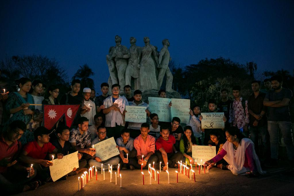 <p>People attend a candlelight vigil for the victims of the US-Bangla plane crash in Dhaka, Bangladesh. At least 50 people were killed on Monday when a passenger plane from Bangladesh crashed and burst into flames as it was attempting to land at Kathmandu's Tribhuvan airport. The plane crash is known to be the worst aviation disaster to hit Nepal in years while investigations had begun into the cause of the crash. (Allison Joyce/Getty Images) </p>