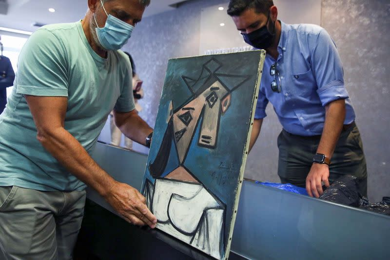 """The paintings """"Woman's Head"""" by Pablo Picasso, and """"Mill"""" by Piet Mondrian are displayed at the Ministry of Citizen Protection in Athens"""