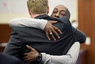 Plaintiff Dewayne Johnson, facing camera, hugs one of his lawyers after hearing the verdict in his case against Monsanto at the Superior Court of California in San Francisco on Friday, Aug. 10, 2018. A San Francisco jury on Friday ordered agribusiness giant Monsanto to pay $289 million to the former school groundskeeper dying of cancer, saying the company's popular Roundup weed killer contributed to his disease. (Josh Edelson/Pool Photo via AP)