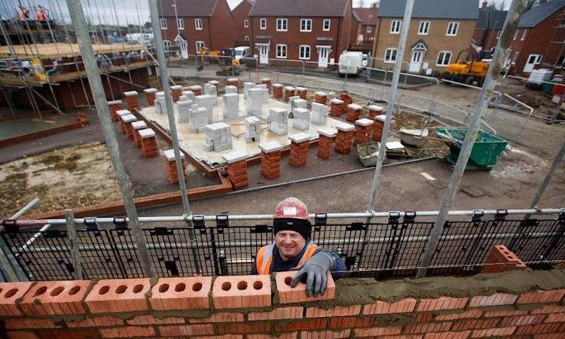 A construction worker lays bricks at a residential property construction site in Cranfield, Bedfordshire.