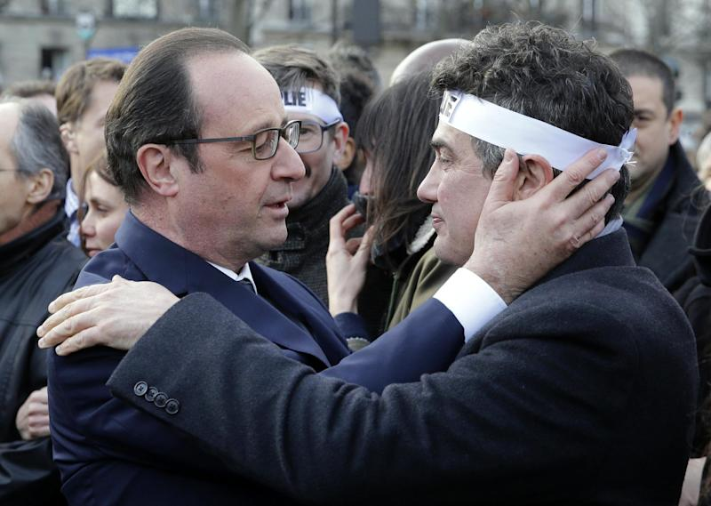 French President Francois Hollande (L) comforts columnist for Charlie Hebdo Patrick Pelloux as they attend the solidarity march in the streets of Paris on January 11, 2015