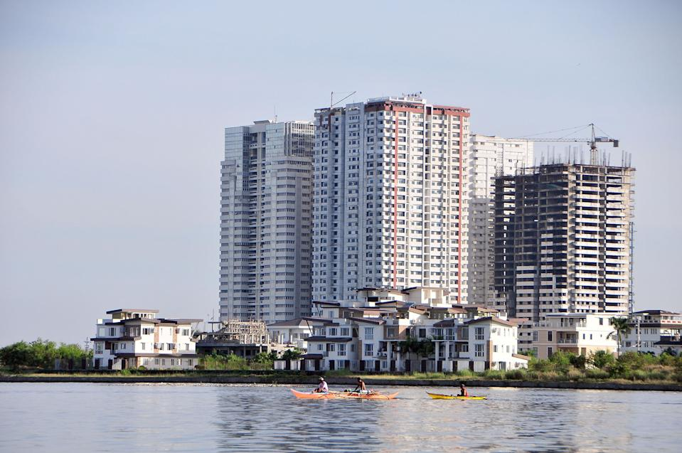 FILE PHOTO: Local fishermen paddle past residential condominiums and townhouses on June 7, 2013 in Manila, Philippines. (Photo by Veejay Villafranca/Getty Images)