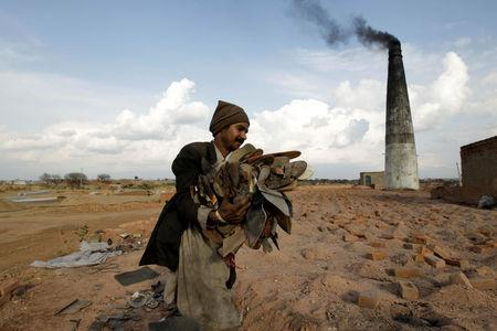 A worker carries shoes to be burned in the kiln of a brick factory in Islamabad, Pakistan March 9, 2017. REUTERS/Caren Firouz