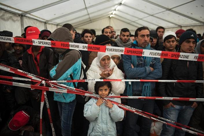Newly arrived immigrants are kept behind a cordon as they wait to be let into a pre-register site in Berlin on October 15, 2015 (AFP Photo/Odd Andersen)