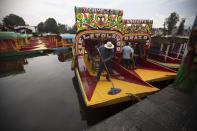 A man mops the deck of a painted wooden boat known as a trajinera, popular with tourists that ply the water canals in the Xochimilco district of Mexico City, during a reopening of activities after a six-month pause due to the COVID-19 pandemic. (AP Photo/Marco Ugarte)